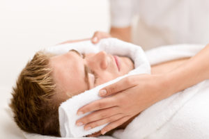 Male cosmetics - luxury spa treatment receiving facial massage