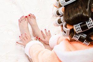 Little girl with manicure and pedicure with hair curlers in bathrobe on bed closeup